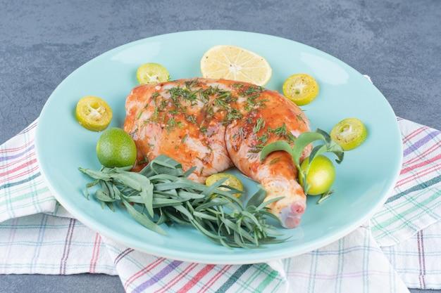 Gemarineerde kip met lemonnd dragon op blauw bord.