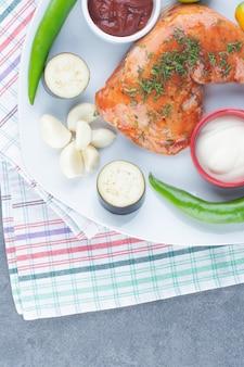Gemarineerde kip op plaat met gesneden groenten.