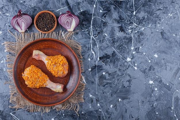 Gemarineerde kippenboutjes op een bord op een jute naast kruiden en ui, op de blauwe tafel.