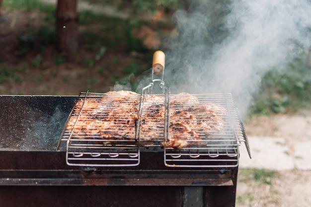 Gemarineerde kippendijen in saus en kruiden koken op een bakplaat op een grill