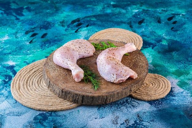 Gemarineerde kippendrumstick met dille op een plank op een onderzetter