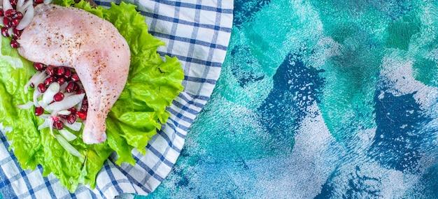 Gemarineerde kippendrumstick met granaatappelpitten op een slablaadjes op een bord op een theedoek op de blauwe achtergrond. hoge kwaliteit foto