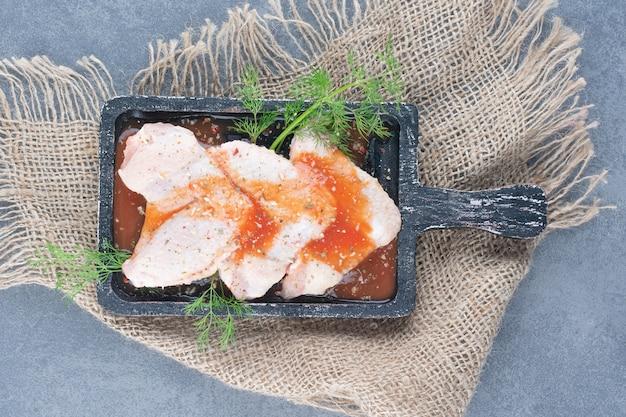 Gemarineerde kippenvleugels met saus op zwart bord.