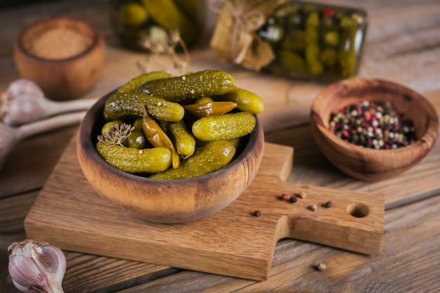 Gemarineerde komkommers augurken met dille en knoflook in glazen pot op de houten tafel