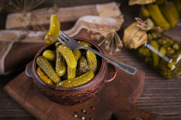 Gemarineerde komkommers augurken met dille en knoflook in glazen pot op donkere houten tafel