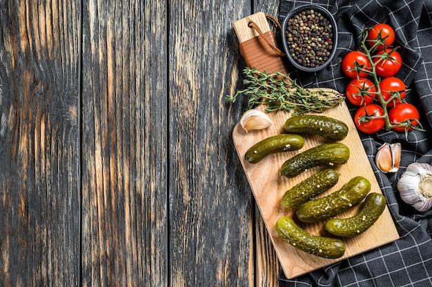 Gemarineerde komkommers augurken op houten snijplank. augurken met mosterd en knoflook. zwarte achtergrond. bovenaanzicht. kopieer ruimte.