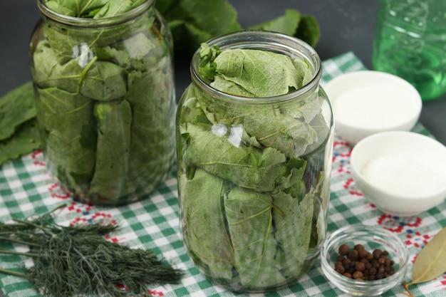 Gemarineerde komkommers in druivenbladeren in potten voor de winter met knoflook en dille, voorbereidende procesclose-up