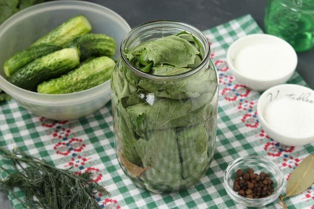 Gemarineerde komkommers in druivenbladeren in potten voor de winter met knoflook en dille, voorbereidingsproces