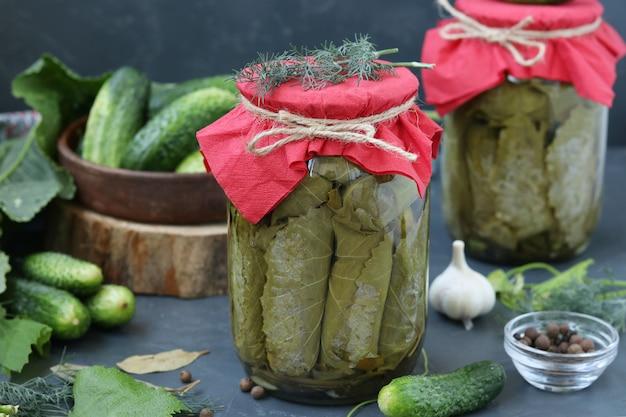 Gemarineerde komkommers in druivenbladeren met knoflook en dille in twee glazen potten op een donkere ondergrond, horizontaal formaat, close-up