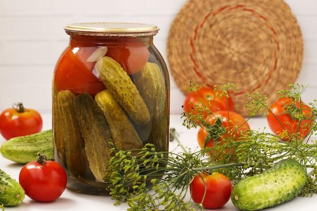 Gemarineerde komkommers met tomaten bevinden zich in glazen potten op een witte achtergrond, oogst voor de winter, close-up, horizontale foto
