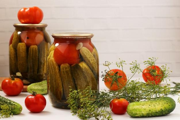 Gemarineerde komkommers met tomaten bevinden zich in glazen potten