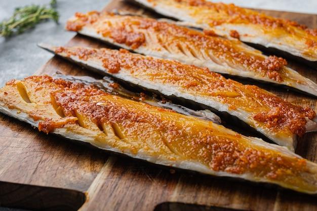 Gemarineerde makreelfilet met paprika en saffraan op grijze ondergrond.