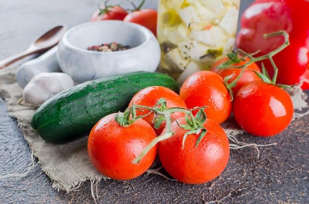 Gemarineerde pittige feta in een pot en groenten voor salade.