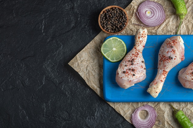Gemarineerde rauwe kippenpoten en kruiden op blauwe houten plank.