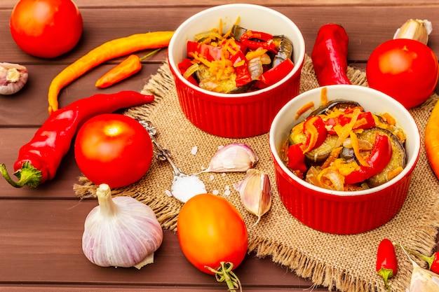 Gemarineerde salade met ingemaakte groenten: aubergine, wortel, peper, tomaat, knoflook