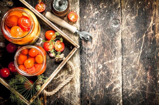 Gemarineerde tomaten met kruiden in een oud bakje. op een houten achtergrond.