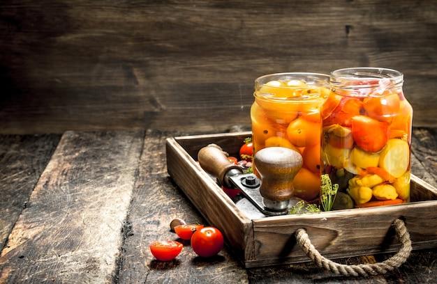 Gemarineerde tomaten met kruiden in een oude bak op een houten tafel.