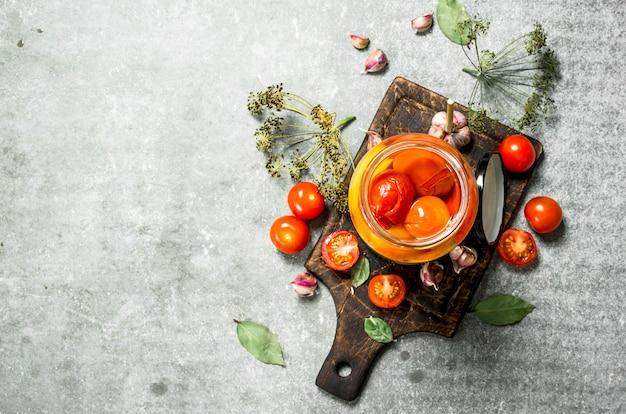 Gemarineerde tomaten met kruiden op een stenen tafel.