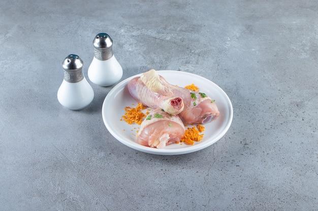 Gemarineerde verse drumstick op een bord naast zout, op het marmeren oppervlak.
