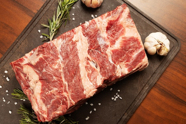 Gemarmerd rundvlees van topkwaliteit. een stuk ligt op een snijplank met rozemarijn en knoflook