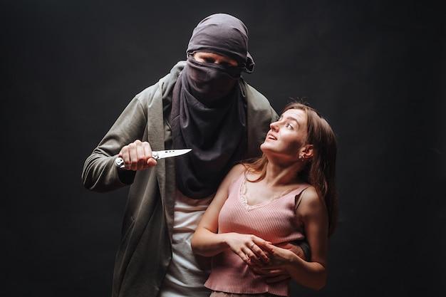 Gemaskerd crimineel dreigend meisje met mes