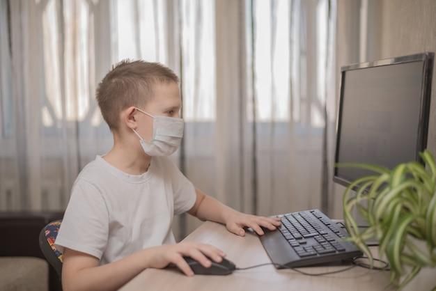 Gemaskerd kind studeert thuis aan tafel en studeert online school op internet