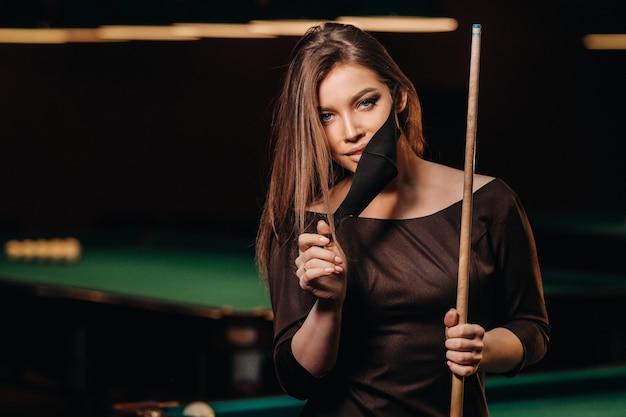 Gemaskerd meisje in een poolclub met een richtsnoer in haar handen