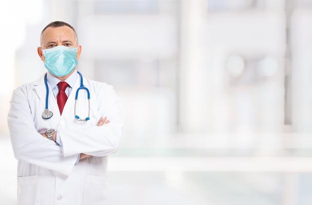 Gemaskerde arts voor een lichte achtergrond tijdens coronavirusepidemie