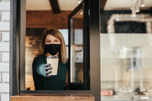 Gemaskerde barista morst koffie door het raam vanwege het coronavirus