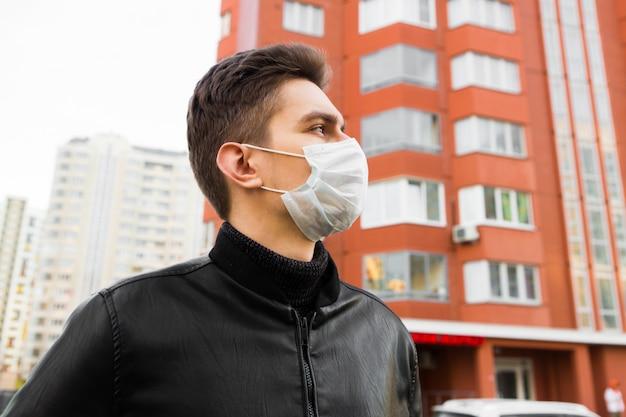 Gemaskerde jonge man op straat. bescherming tegen ziekte en virus.