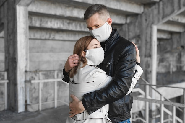 Gemaskerde man en vrouw omarmen coronavirus covid19