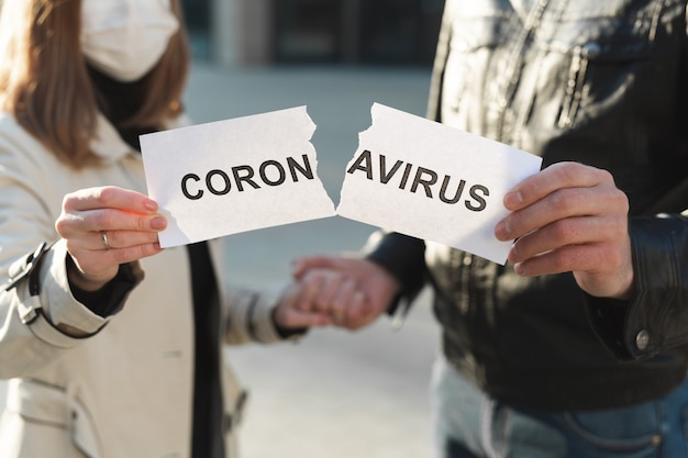 Gemaskerde man en vrouw scheuren een papier met het opschrift coronavirus open en houden elkaars hand vast