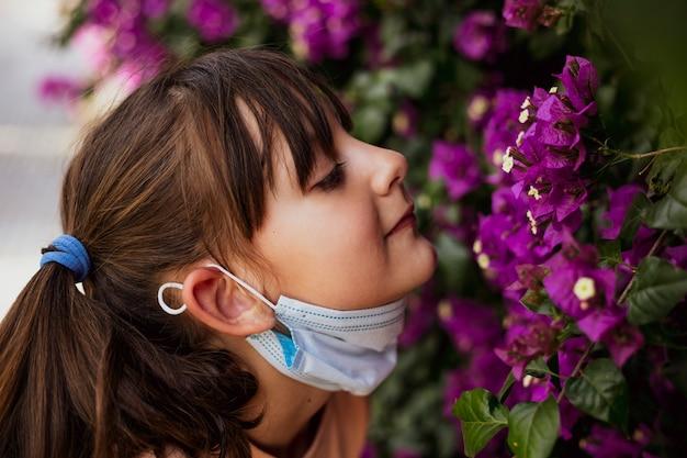 Gemaskerde meisjes ruikende bloemen in de tuin