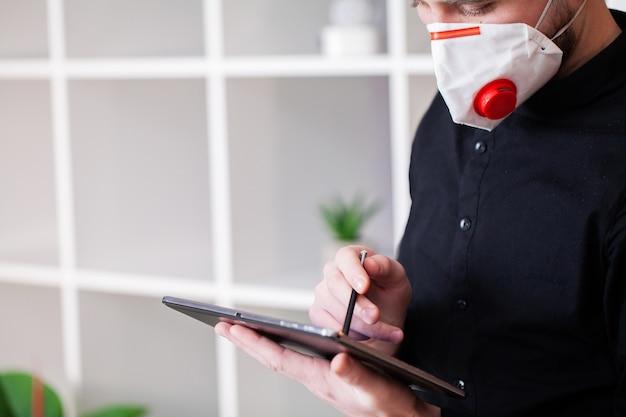 Gemaskerde mens die aan tablet op bedrijfkantoor werken