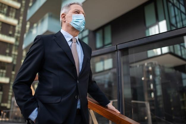 Gemaskerde oudere zakenman lopen op een trap, covid coronavirus concept