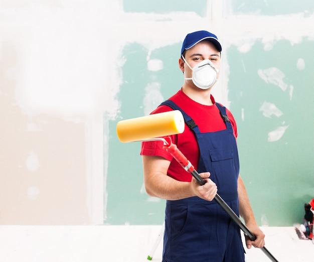 Gemaskerde schilder aan het werk in een appartement, renovatie en thuis schilderen tijdens coronavirus pandemie