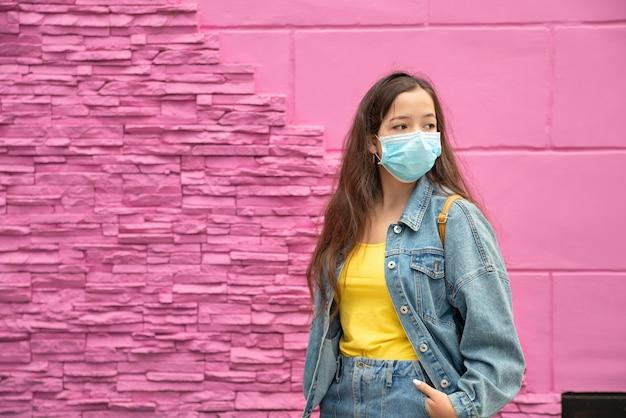 Gemaskerde tienermeisje - bescherming tegen griepvirus. meisje op een roze achtergrond met kopie ruimte.