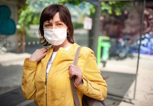 Gemaskerde vrouw buitenshuis tijdens coronavirus-pandemie