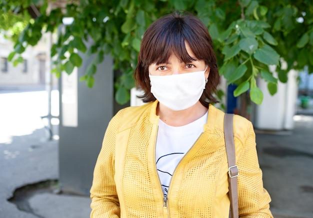 Gemaskerde vrouw die buiten poseren tijdens coronavirus-pandemie