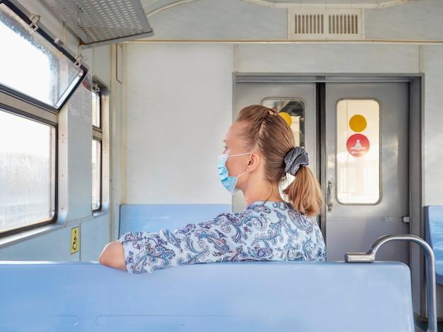 Gemaskerde vrouw in een trein. veiligheid op een openbare plaats tijdens de epidemie van covid-19