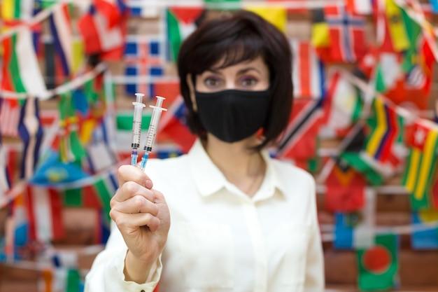 Gemaskerde vrouw met spuit in de hand, coronavirusvaccinatieconcept. vervagen