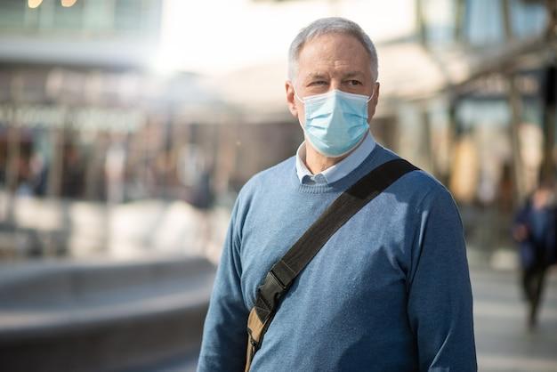 Gemaskerde zakenman die buiten loopt om op het werk te gaan, levensstijlconcept van coronavirusmensen