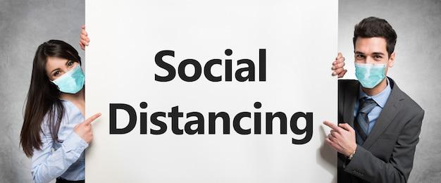 Gemaskerde zakenmensen houden een wit bord met de tekst sociale afstand