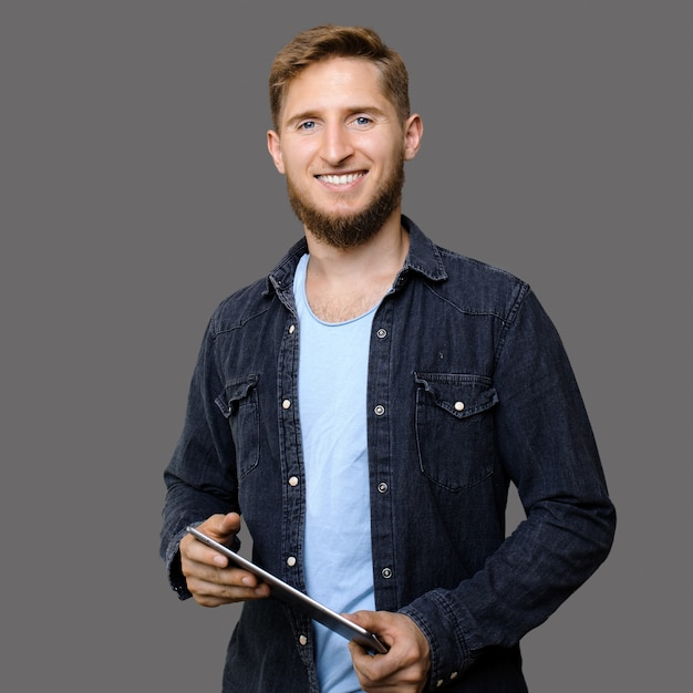 Gember blanke man met baard die een tablet vasthoudt en it-diensten promoot terwijl hij op een grijze muur glimlacht