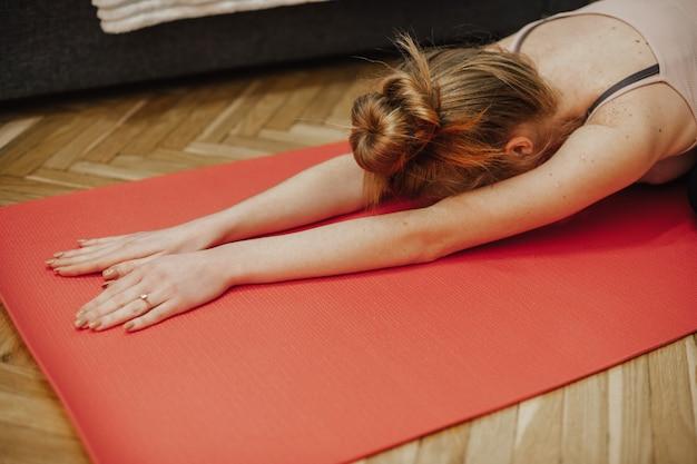 Gember blanke vrouw die zich uitstrekt op een rode loper op de vloer tijdens het beoefenen van yoga
