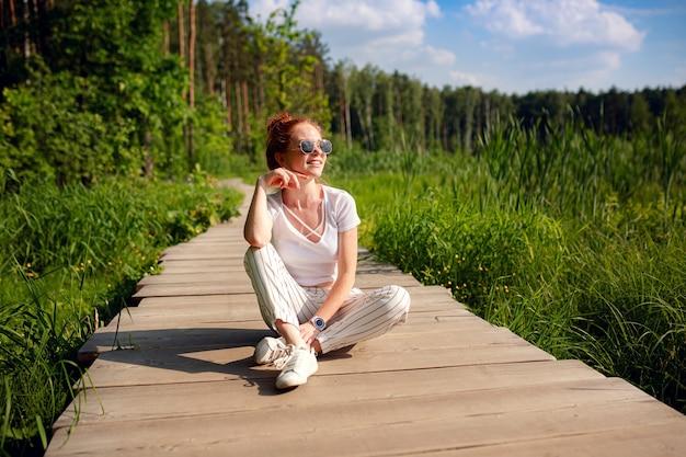 Gember charmante vrouw jonge mooie bos groen. kaukasisch meisje ontspannen en genieten van het leven in de natuur buiten.