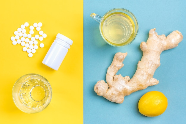 Gember, citroen, thee, pillen, glas op blauwe en gele achtergrond. alternatieve remedies en traditionele pillen om verkoudheid en griep te behandelen.