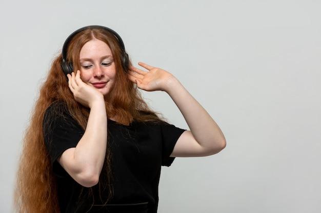 Gember dame luisteren naar muziek in zwarte jurk op grijs