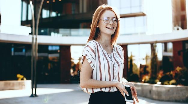 Gember dame met sproeten en bril poseren buiten met een telefoon in een zonnige dag