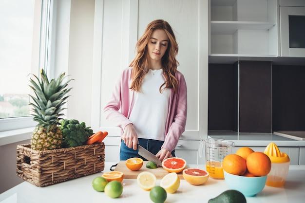 Gember dame met sproeten fruit snijden voordat ze het sap uitknijpen